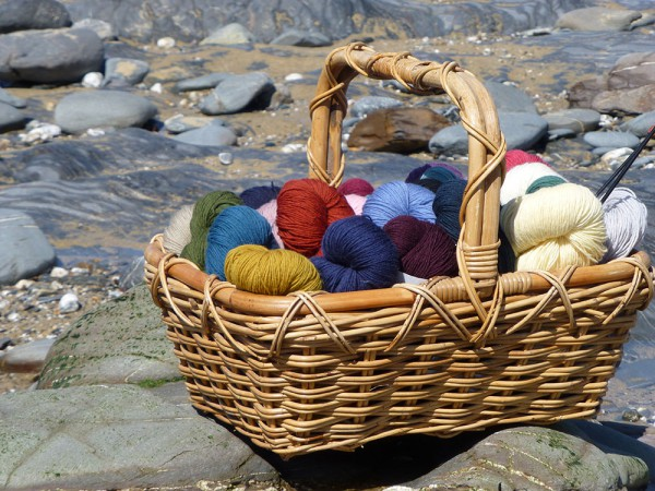 Basket of Guernsey knitting yarns on a pebbly beach