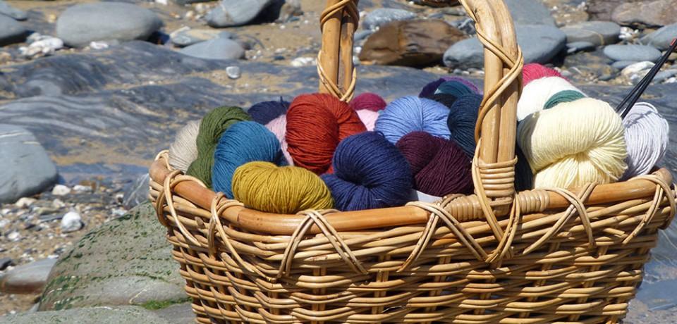 Basket of Guernsey knitting yarns on a pebbly beach