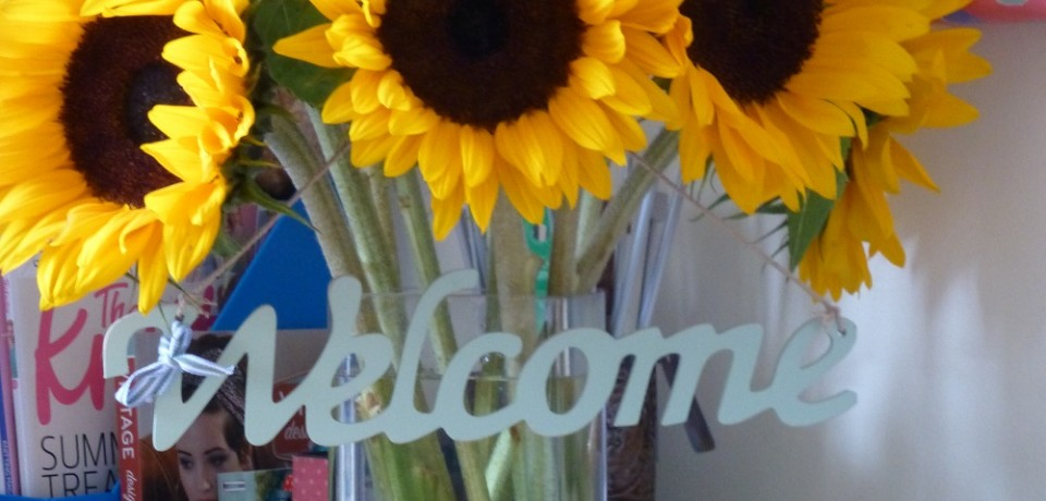 Sunflowers on desk with Welcome