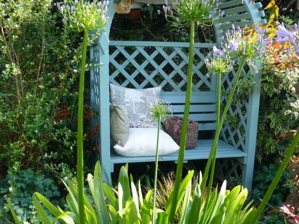 Blue garden bench with cushions and knitting